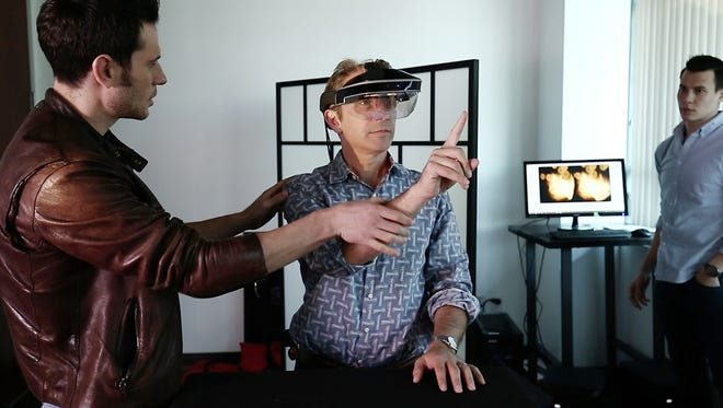 USA TODAY reporter Marco della Cava gets guidance from Meta founder Meron Gribetz, left, on how to manipulate holograms in space using the company's new Meta 2 augmented reality glasses.