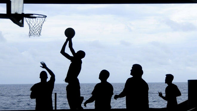 Basketball players are silhouetted on the court.