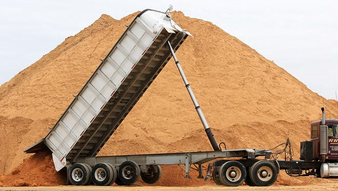 In this photo taken Feb. 13, 2012, a truck dumps a load of silica sand at Modern Transport Rail loading terminal in Winona, Minn. Winona County, Minnesota's only county to ban the mining of silica sand for use by the oil and gas industry in hydraulic fracturing, goes to court Thursday, May 10, 2018, to defend the ban.