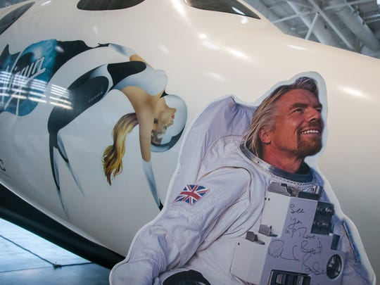 A cutout of businessman Richard Branson is positioned in front of a replica of Virgin Galactic's SpaceShipTwo, the suborbital spaceplane created for space tourism, at Spaceport America's first open house.