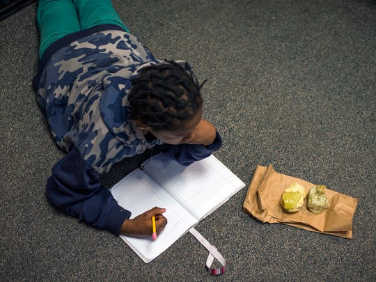 Davial Pitt, 11, lays on the floor while using rocks as writing prompts during a writing workshop at Woodrow Wilson Elementary School.