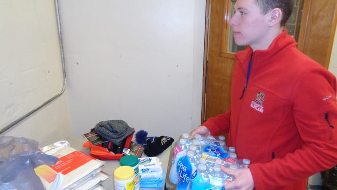 Michael Schultz unloads cases of water collected at St. Francis of Assisi Church in Hillcrest. He is a confirmation student who helped organize a collection for homeless people.