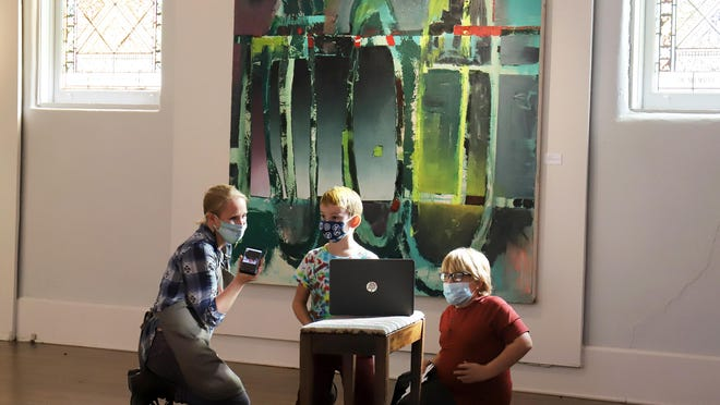Amy Scoggins, left, Jude Marshall and Noah Lohtinen, talk to Fayetteville artist Jody Travis Thompson via video conference, Monday, Nov 16, during the CAE's Homseschool and Afterschool Program held in front of Thompson' s painting on display in the CAE Main Gallery. The program includes studio work and exhibition tours. Jude is the 7-year-old son of Asherlee and Jeremy Marshall and Noah is the 8-year-old son of Maggie Lohtinen.