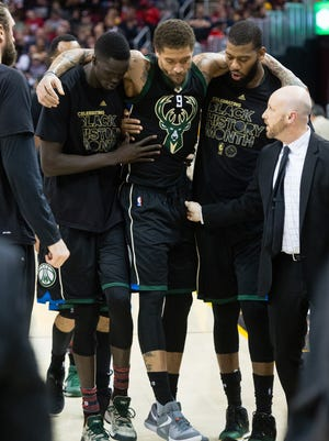 Michael Beasley is helped off the court Feb. 27 in Cleveland by teammates Thon Maker (left) and Greg Monroe (right).