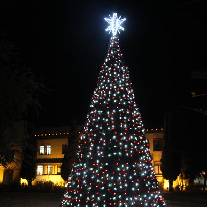 A 30-foot Christmas tree is decorated on the lawn next