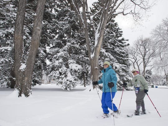 Georgia Locker and Marty Tharp take advantage of recent snowfall to snowshoe in City Park Friday, March 18, 2016. Around six inches of snow fell across the Fort Collins area Thursday into Friday morning.