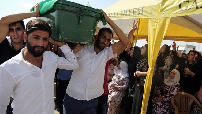 Mourners carry a victim's coffin at a funeral for dozens of people killed in Saturday's bomb attack targeting an outdoor wedding in Gaziantep, southeastern Turkey, Sunday, Aug. 21, 2016. The suicide attacker was a child as young as 12 employed by the Islamic State.