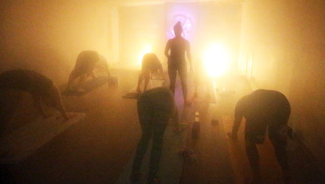 Kat Mark, center, leads Smile High Club members in a hot yoga class Saturday in West El Paso.