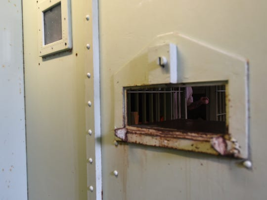Inmates seen through a door in the Coshocton County Jail. The facility, built to house 15 of inmates, housed 75 on Sept. 15.