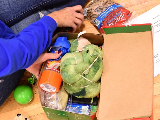 Laurie Wells works to get as many items as possible in to a box for Operation Christmas Child on Friday, Nov. 4 at the Licking County Family YMCA. The collected items were packaged by volunteers to be sent to children around the world for Christmas. Items included toys, clothes, and personal care items.