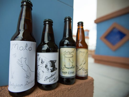 Local Las Cruces home brewed beer created by Nora Brown and Eric Brekke features Brekke's handmade labels inspired by their respective felines.