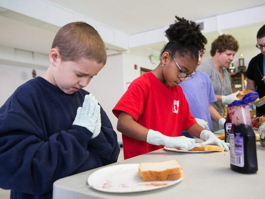 In this 2016 file photo, students are shown preparing peanut butter and jelly sandwiches that were given away during an All Saints Catholic School Serve-a-Thon.