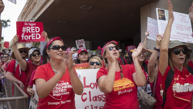 Supporters march past the executive tower during a rally, April 30, 2018, at the Arizona Capitol in Phoenix on the third day of the Arizona teacher walkout.