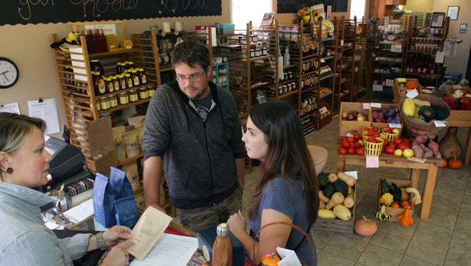 Kristin Henderson, left, market manager of Local Bounty Coshocton on Ohio 83 in Coshocton, speaks to Damon Mullen and Sarah McCloud, of Sraddha Coffee Roasting Company, about becoming a vendor. The USDA is awarding the market a $100,000 grant to expand local food efforts. The market makes locally-grown commodities available to consumers.