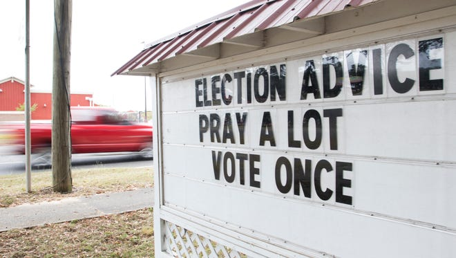 A sign gives a little Election Day advice in Pensacola on Tuesday, November 8, 2016.