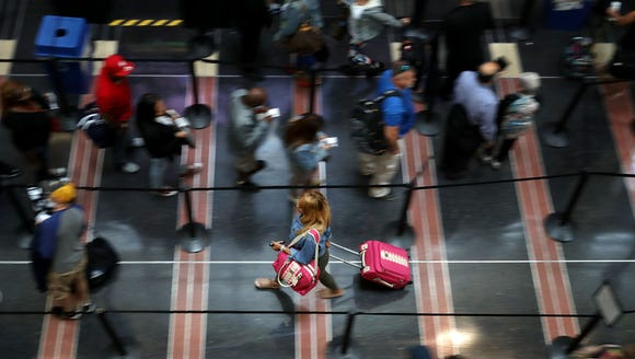 Travelers move through a  Transportation Security Administration
