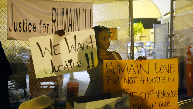 Brittany Jones of Avondale holds signs outside the William H. Patterson Elks Lodge on Monday in Phoenix.  Demonstrators marched to a Phoenix police station in protest of a shooting last week that left an unarmed man dead.