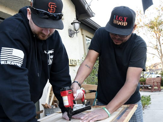 Veterans Joel Souza, of Clovis, and Rolando Corral work on a wooden flag at Corral's Visalia home Tuesday afternoon.