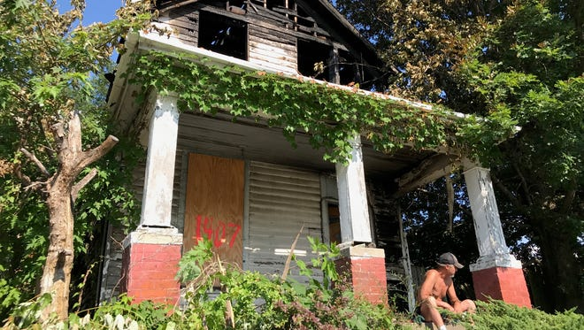 A shirtless man sits on the porch of 1407 N. First Ave. Sunday afternoon. The home was damaged in a fire early Saturday morning. The Evansville Fire Department is investigating the blaze as arson.