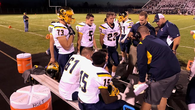 Grand Ledge players huddle around the coaching staff in the first half of the Comets' victory Friday night, Oct. 20, 2017.