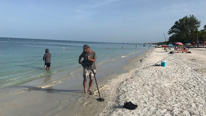 Steve Gulde of Fort Myers prepares to use his metal detector underwater while Charles Dorn, of Orlando, tries his luck fishing at Bonita Beach Sunday morning. Water at the beach was crystal clear with no evidence of the blue-green algae or red tide that has plagued other areas around SWFL in  the past month.
