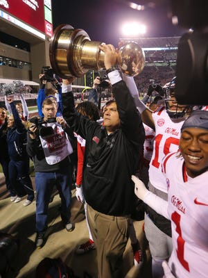 Ole Miss interim head coach Matt Luke holds the Egg Bowl trophy following the Rebels' 31-28 victory over Mississippi State Thursday in Starkville.