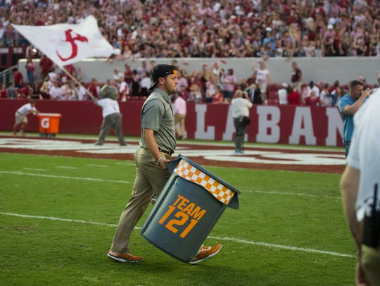 A Tennessee assistant walks of the field with the trash