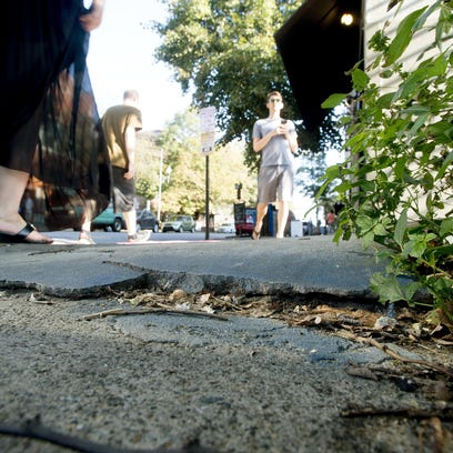 Pedestrians walk past cracked and uneven sidewalk along Broadway between College and Walnut streets Wednesday. The city has painted some portions of the sidewalk to warn walkers.
