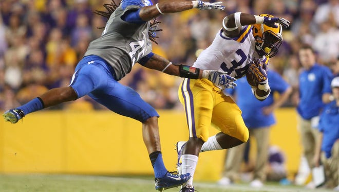 Oct 18, 2014; Baton Rouge, LA, USA; LSU Tigers running back Darrel Williams (34) carries the ball past Kentucky Wildcats linebacker Josh Forrest (45) in the first half at Tiger Stadium. Mandatory Credit: Crystal LoGiudice-USA TODAY Sports