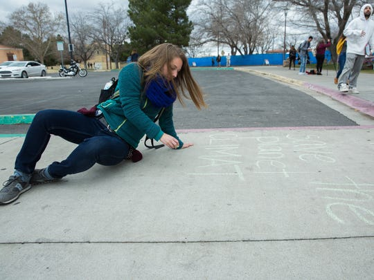 "Carol Tessein, a student at New Mexico State University, writes ""Save the Planet Climate Change is Real,"" in chalk on the sidewalk outside of Corbett Center, Tuesday, February 14, 2017, before a diverse group of students march down the International Mall at NMSU to protest Trump administration policies."