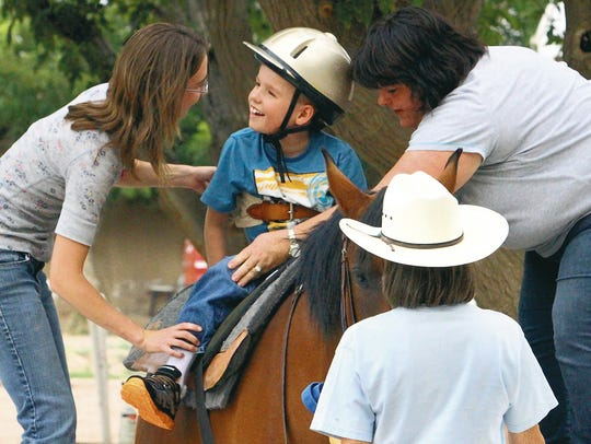 Ty Cox, 8, beams as he's helped onto a horse by occupational
