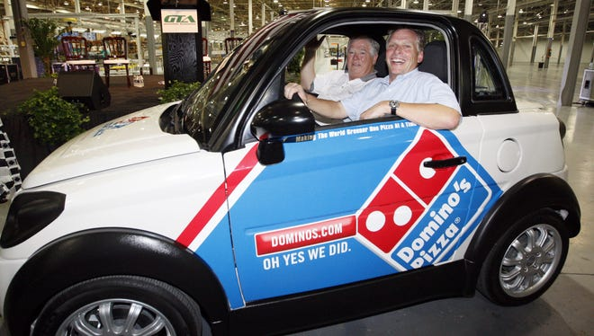 Former Mississippi Gov. Haley Barbour, left, and then-GreenTech Automotive founder Terry McAuliffe take a spin in the plant after the unveiling of the company's new electric MyCar in Horn Lake on July 5, 2012. Domino's Pizza bought a fleet of the cars. Now Mississippi's auditor is asking the failing car company to return the $5 million it borrowed.