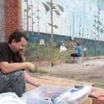 In May 2014, Louisiana Tech associate professor of art Nicholas Bustamante created a mural for a building on DeSiard Street as part of the downtown revitalization. In the background Tech students work on the mural. An exhibit of Bustamante's murals in six northeastern Louisiana towns is showing at Parish Press in Ruston.