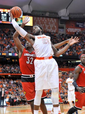 Syracuse forward Rakeem Christmas grabs a rebound over Louisville forward/center Chinanu Onuaku during the second half of Wednesday's game. Syracuse won, 69-59.
