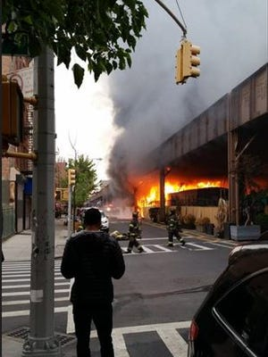 Firefighters battle a fire under the Metro-North railroad tracks at Park Avenue and East 119th Street in New York, Tuesday, May 17, 2016, In this photo provided by Ben Parkin. Train service into and out of Grand Central was disrupted due to the fire.