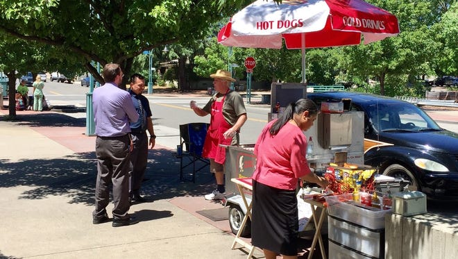 Randy Simpson talks to customers of his hot dog stand in front of downtown Redding post office on Yuba Street.
