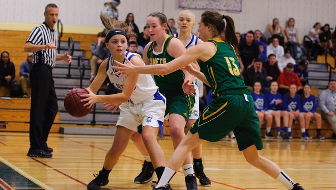 Colchester's Emmakate O'Donnell (14) looks to pass the ball past BFA's Caitlyn Dasaro (13) during the girls basketball game between the BFA St. Albans Comets and the Colchester Lakers at Colchester High School on Friday night December 15, 2017.
