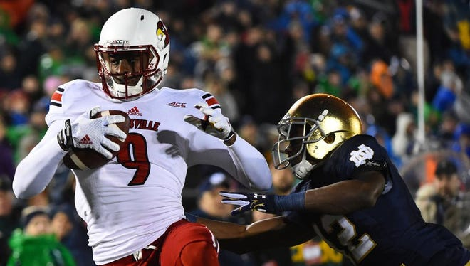 Nov 22, 2014; South Bend, IN, USA; Louisville Cardinals wide receiver DeVante Parker (9) makes a touchdown catch against Notre Dame Fighting Irish linebacker Michael Deeb (42) during the third quarter at Notre Dame Stadium. Mandatory Credit: Mike DiNovo-USA TODAY Sports