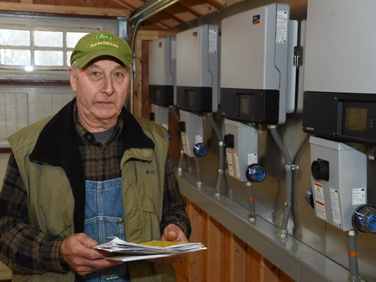 William Werba of Milton holds correspondence he has had with Central Hudson while beside the electronics he had installed that are necessary to convert energy from solar panels to feed into the electrical grid on Dec. 15, 2015.
