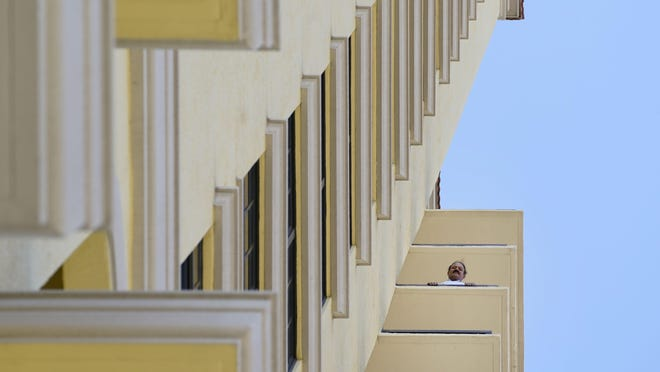 Deepak Laroia looks down from his 12th floor balcony at Two City Plaza Thursday in downtown West Palm Beach.