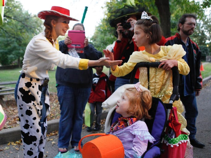 Volunteers portraying Toy Story characters greet Elsie Wright, center, and Ella Wright as they participate in the special Halloween party for Kosair Charities children. Elsie has Angelman Syndrome and Ella has cerebral palsy. Oct. 16, 2013
