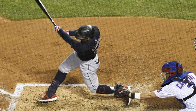 Cleveland Indians' Francisco Lindor (12) hits a one-run double against the Chicago Cubs during the third inning of a baseball game, Tuesday night, Sept.15, 2020, in Chicago.