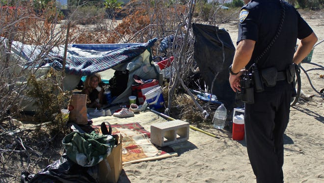 Palm Springs police officer Barron Lane inspects a homeless camp on Tahquitz Canyon Way in this Desert Sun file photo.