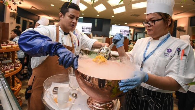 Hyatt Regency Guam employees, Angelo Lacson, left, and Abigail Pineda, use liquid nitrogen to prepare their version of mango sorbet to serve to attendees during the Pastries in Paradise event at the Guam Museum on Thursday, May 11, 2017.
