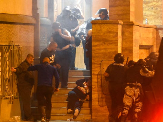 People react as a stun grenade explodes by a parliament entrance, guarded by police, during clashes with protesters in Skopje, Macedonia, Thursday, April 27, 2017. Chaos swept into Macedonia's parliament Thursday as demonstrators stormed the building and attacked lawmakers to protest the election of a new speaker despite a months-old deadlock in efforts to form a new government.