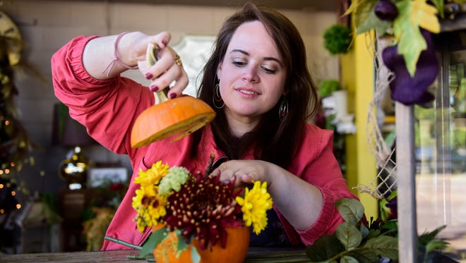 Kayla Hathaway, general manager at Conversation Piece, explains how a pumpkin centerpiece is constructed. The store offers make-and-take classes where customers can create their own decorations