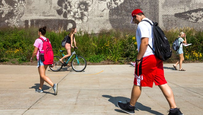 Students walk past a mural on the University of Wisconsin-Stevens Point's College of Natural Resources building Tuesday, September 12, 2017, in Stevens Point, Wis.