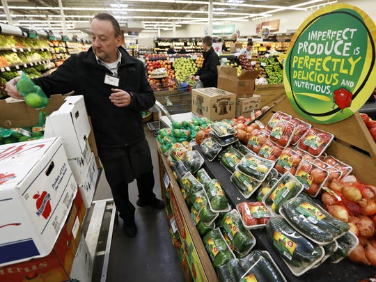 Dave Ruble stocks the imperfect produce section at the Hy-Vee grocery store in Urbandale, Iowa.