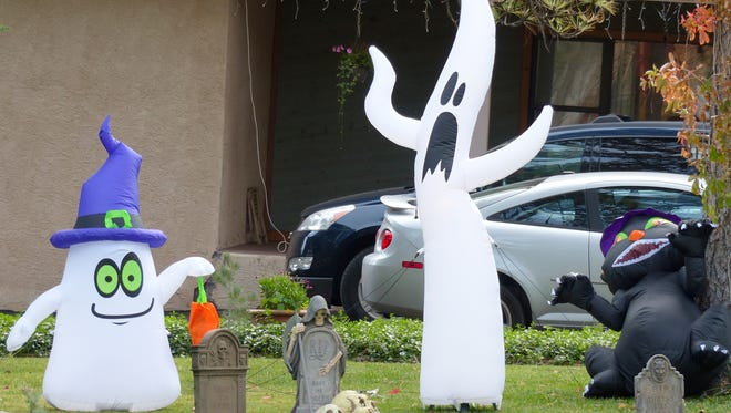 A trio of Halloween characters and a miniature graveyard wait for Halloween night.
