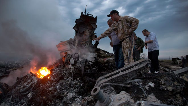 People inspect the crash site of a passenger plane near the village of Grabovo, Ukraine, Thursday, July 17, 2014. Ukraine said a passenger plane carrying 295 people was shot down Thursday as it flew over the country, and both the government and the pro-Russia separatists fighting in the region denied any responsibility for downing the plane. (AP Photo/Dmitry Lovetsky)